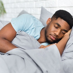 Man sleeping peacefully in bed with gray sheets