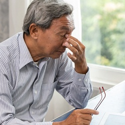 Tired man sitting at desk and pinching bridge of nose